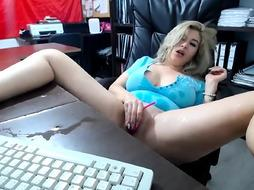 Killer, ash-blonde cougar is stroking with a hefty faux-cock while alone in her fresh office